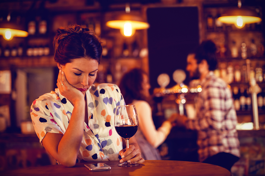 Upset woman ignoring affectionate couple in pub